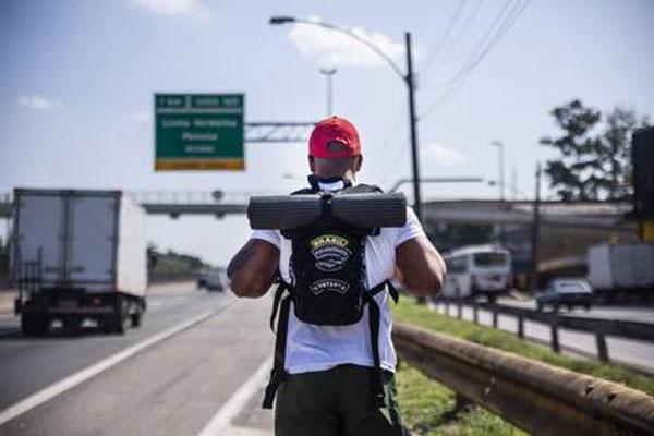 Homem com mochila em estrada