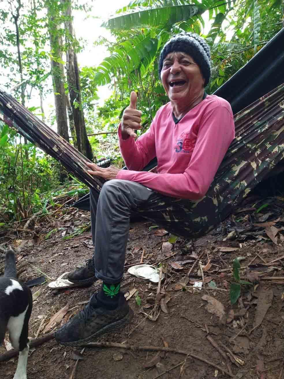 idoso sentado rede balanço sorrindo fazendo sinal positivo dedo