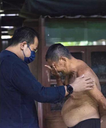 homem conversa idoso chorando dentro barraco madeira