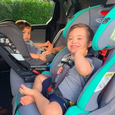 garoto down e irmão em cadeiras carro