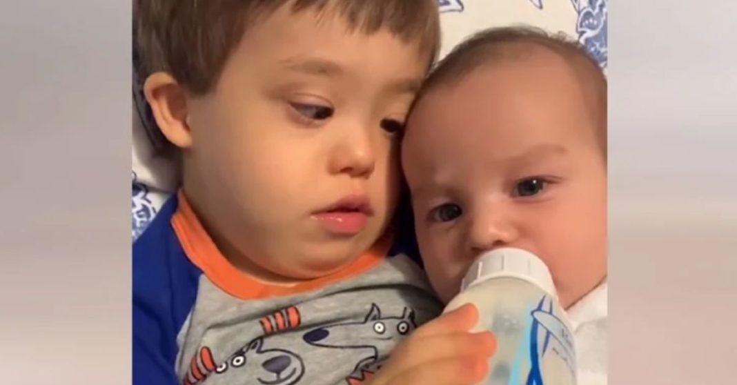 menino Down dá mamadeira irmão mais novo
