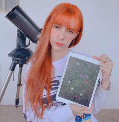 Jovem segurando iPad com imagem de asteroides