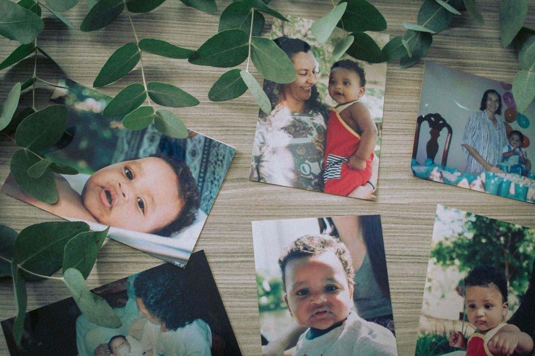 fotos criança negra sobre mesa rodeada folhas verdes