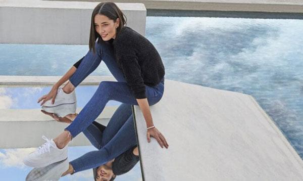 Modelo com calça jeans da Malwee sentada em frente a espelho d'água