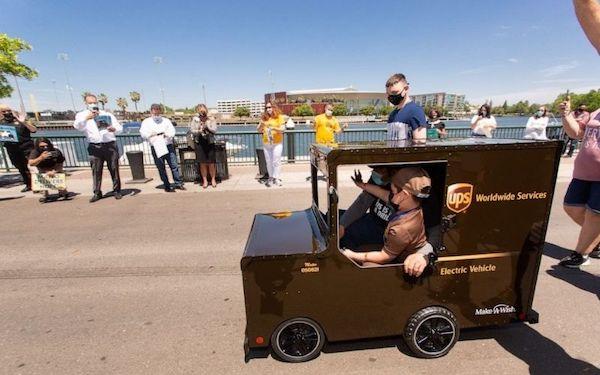 menino acenando em mini caminhão de entrega