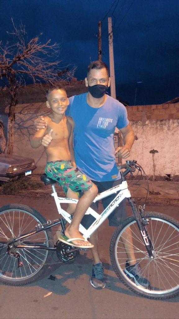 sargento doa bicicleta a menino que perdeu pai assassinado; ambos posam para a foto