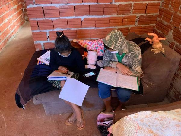 Irmãos estudando em casa de tijolo