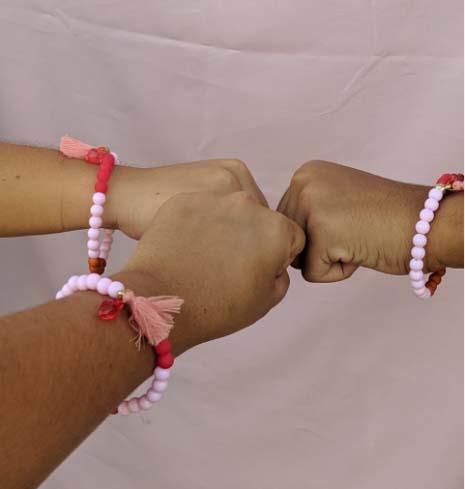punhos de três meninas usando pulseira com bolinhas representam ciclo menstruação
