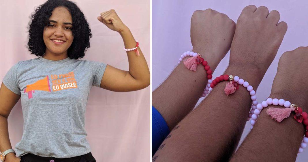 jovem negra erguendo braço com pulseira simbolizando ciclos menstruais