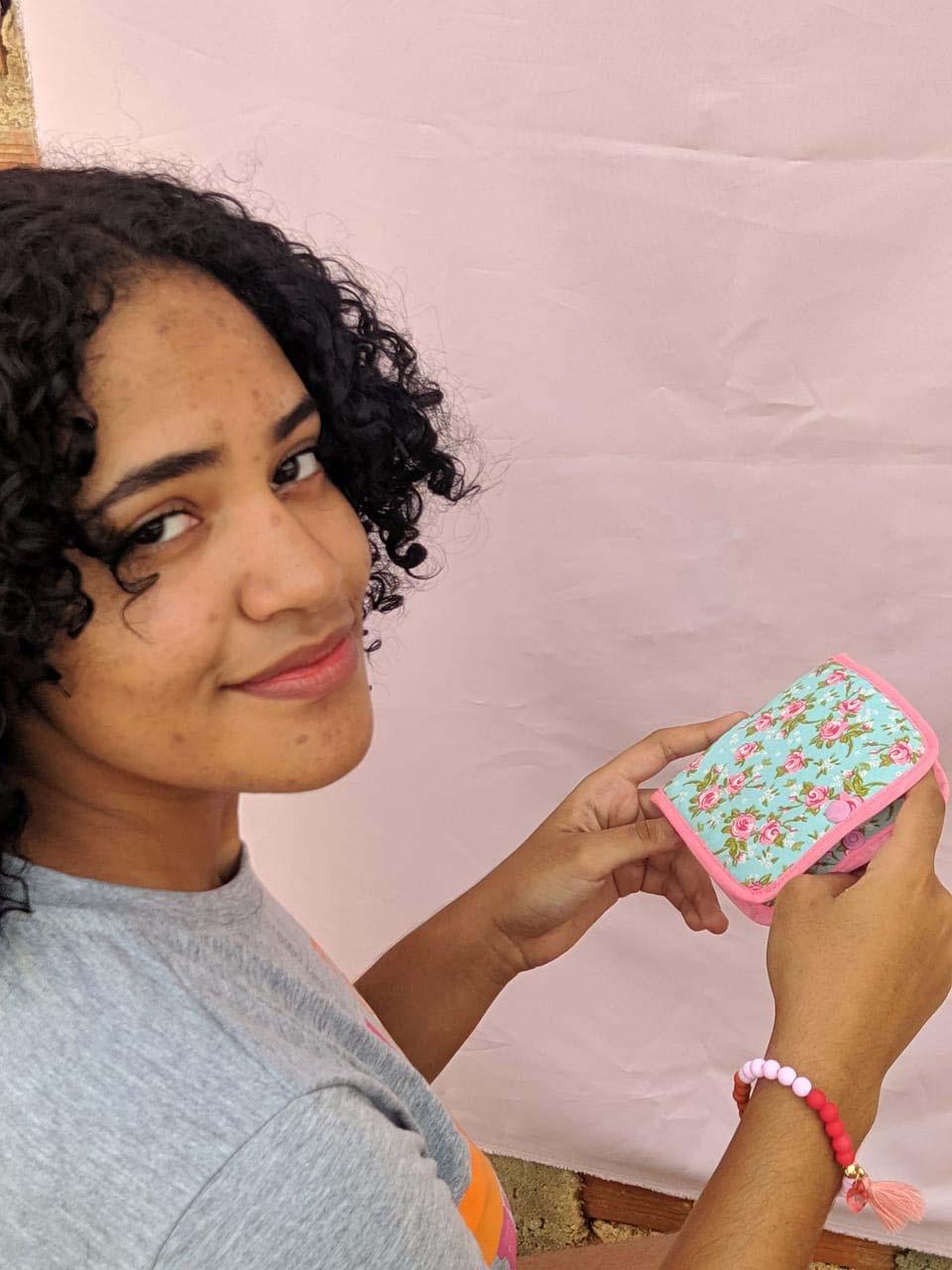 menina negra abrindo carteira estampa flores