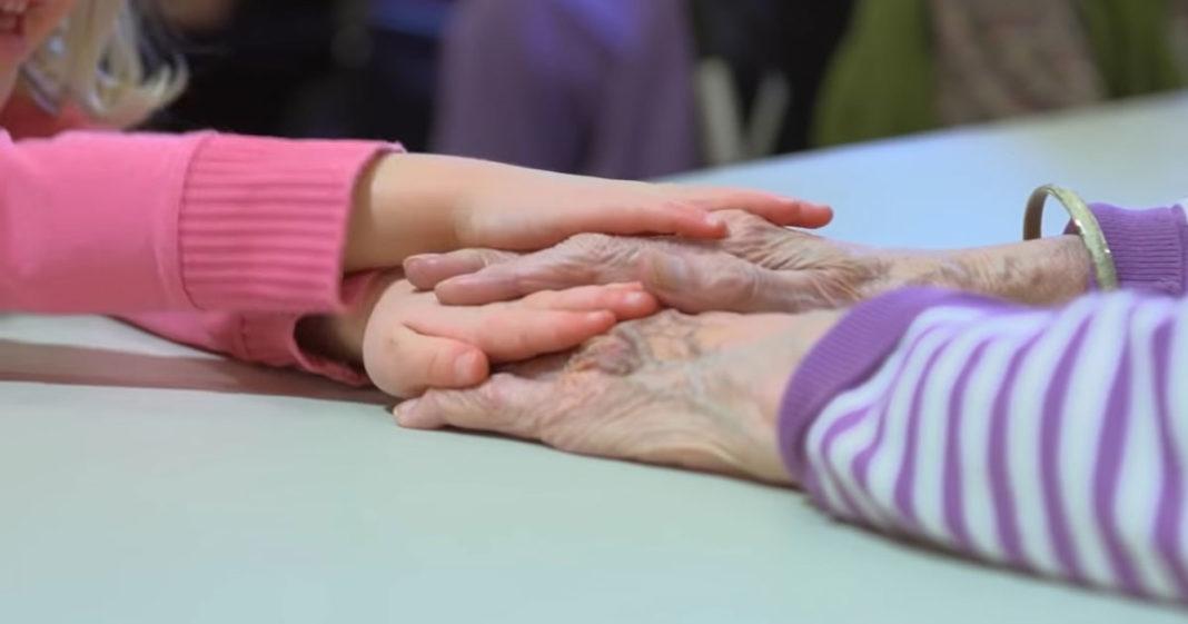 Idosa e criança dando as mãos