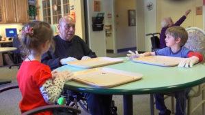 Idoso conversando com crianças em mesa em creche