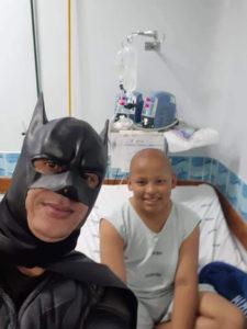 Homem fantasiado de Batman em hospital com jovem doente