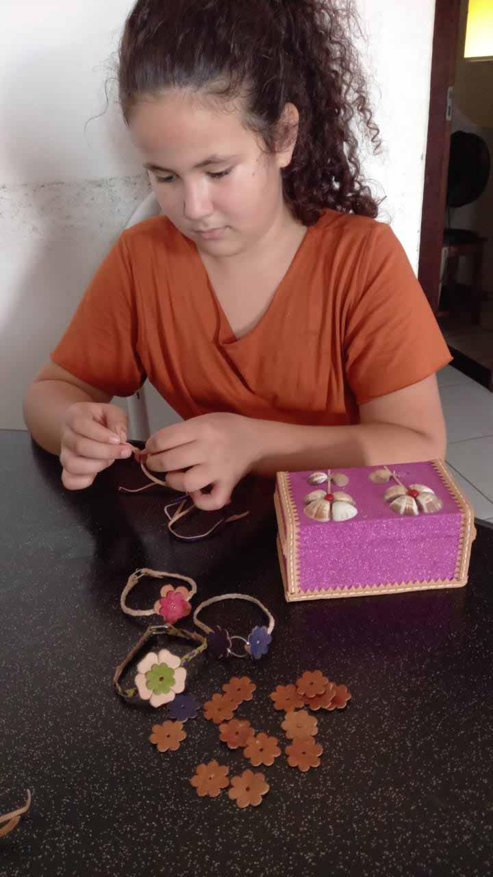 menina produz pulseiras couro feitas a mão