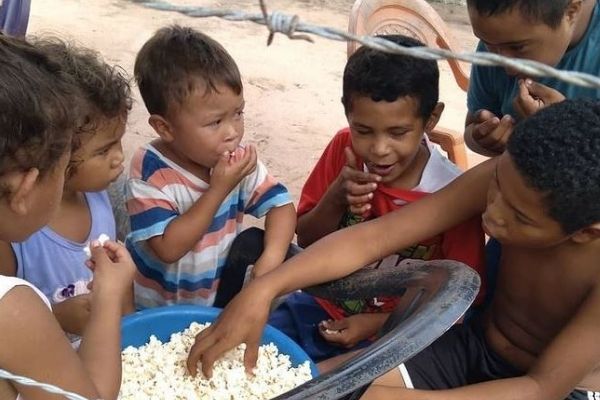crianças comendo pipoca