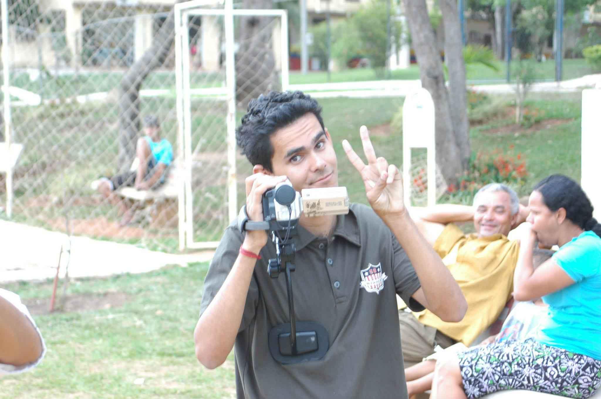rapaz segurando filmadora fazendo sinal positivo outra mão parque