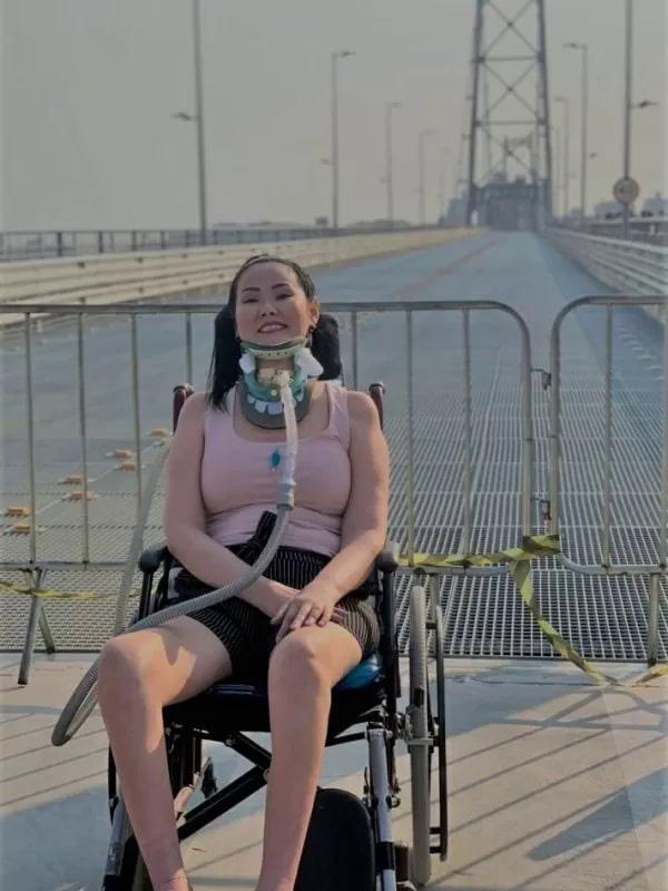 mulher com ela sentada cadeira de rodas sobre ponte