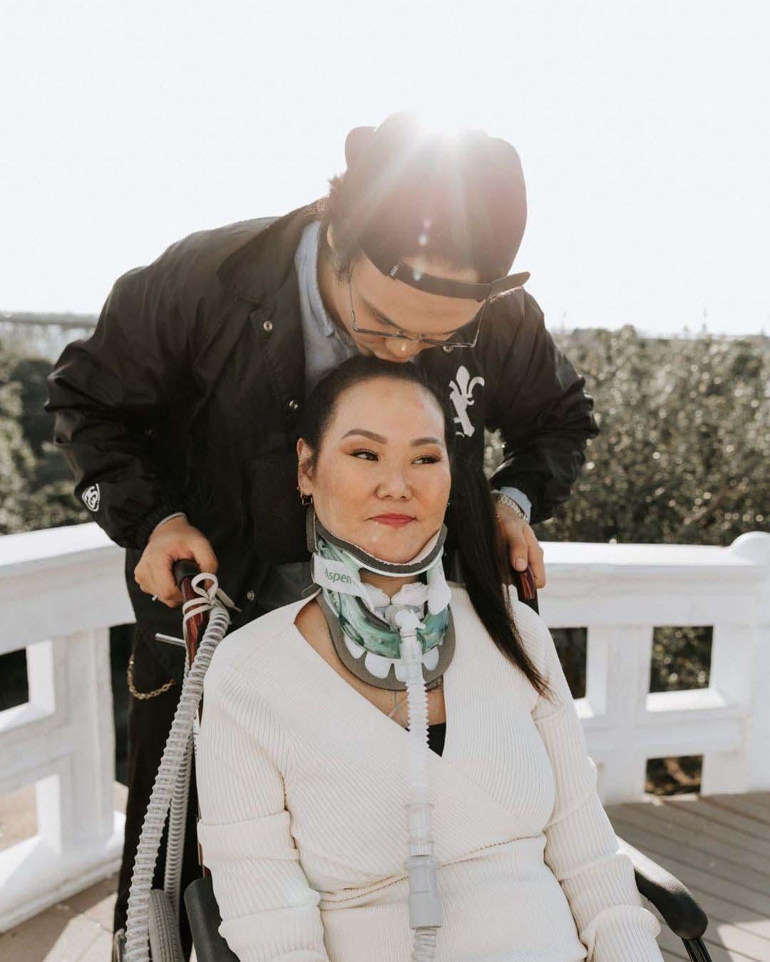 filho beija mãe testa sentada cadeira de rodas