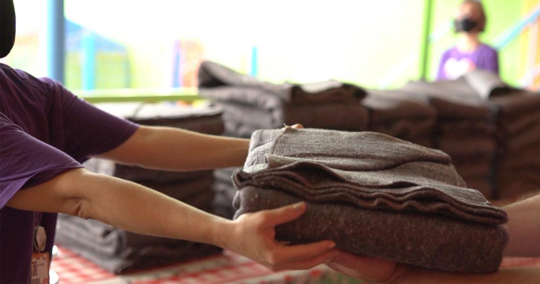mulher organiza cobertores moradores de rua