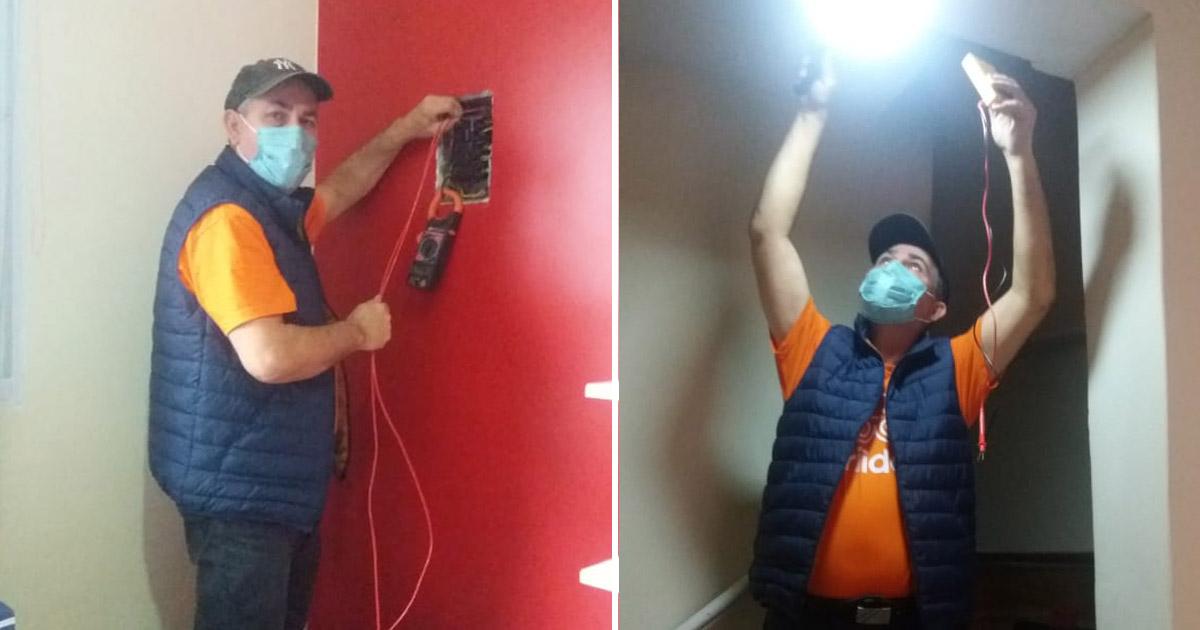 eletricista consertando fiacao elétrica parede vermelha