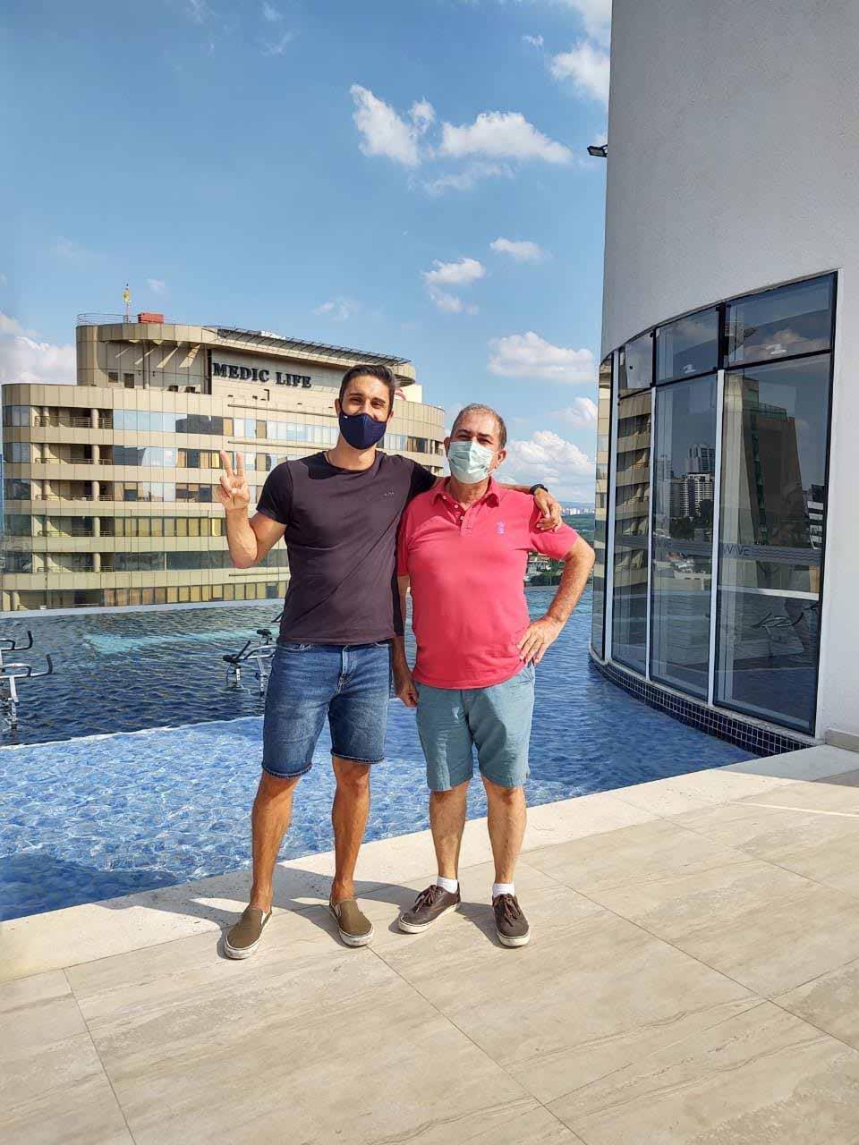 filho e pai beira piscina prédio