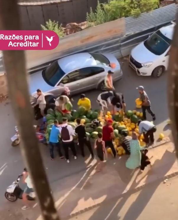 multidão ajuda comerciante recolher frutas de banca que tombou na rua