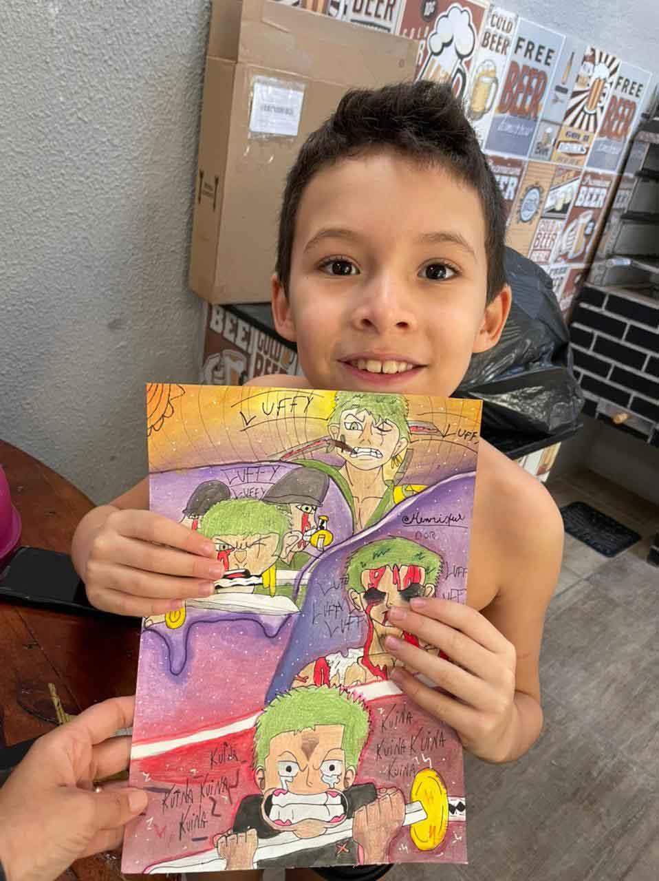 menino segurando desenho duas mãos