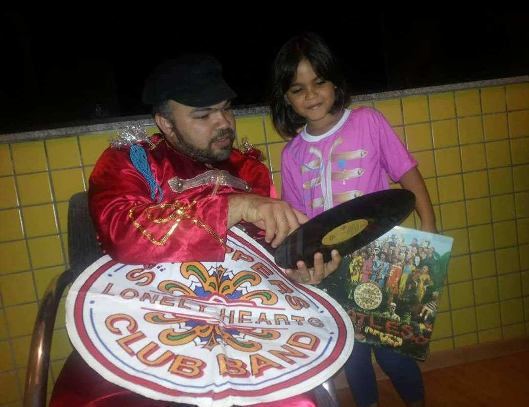 pai mostra disco dos beatles para a filha