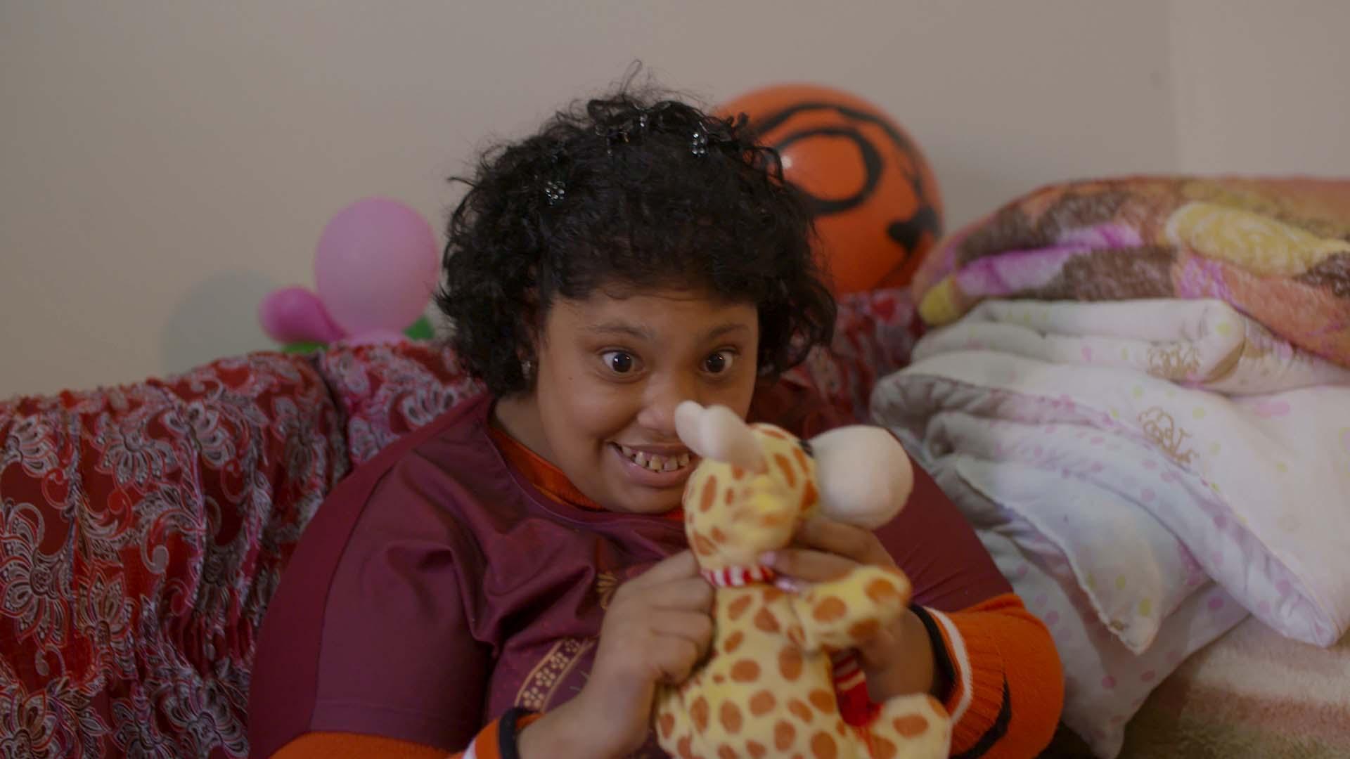 menina microcefalia brinca girafa pelúcia sentada sofá