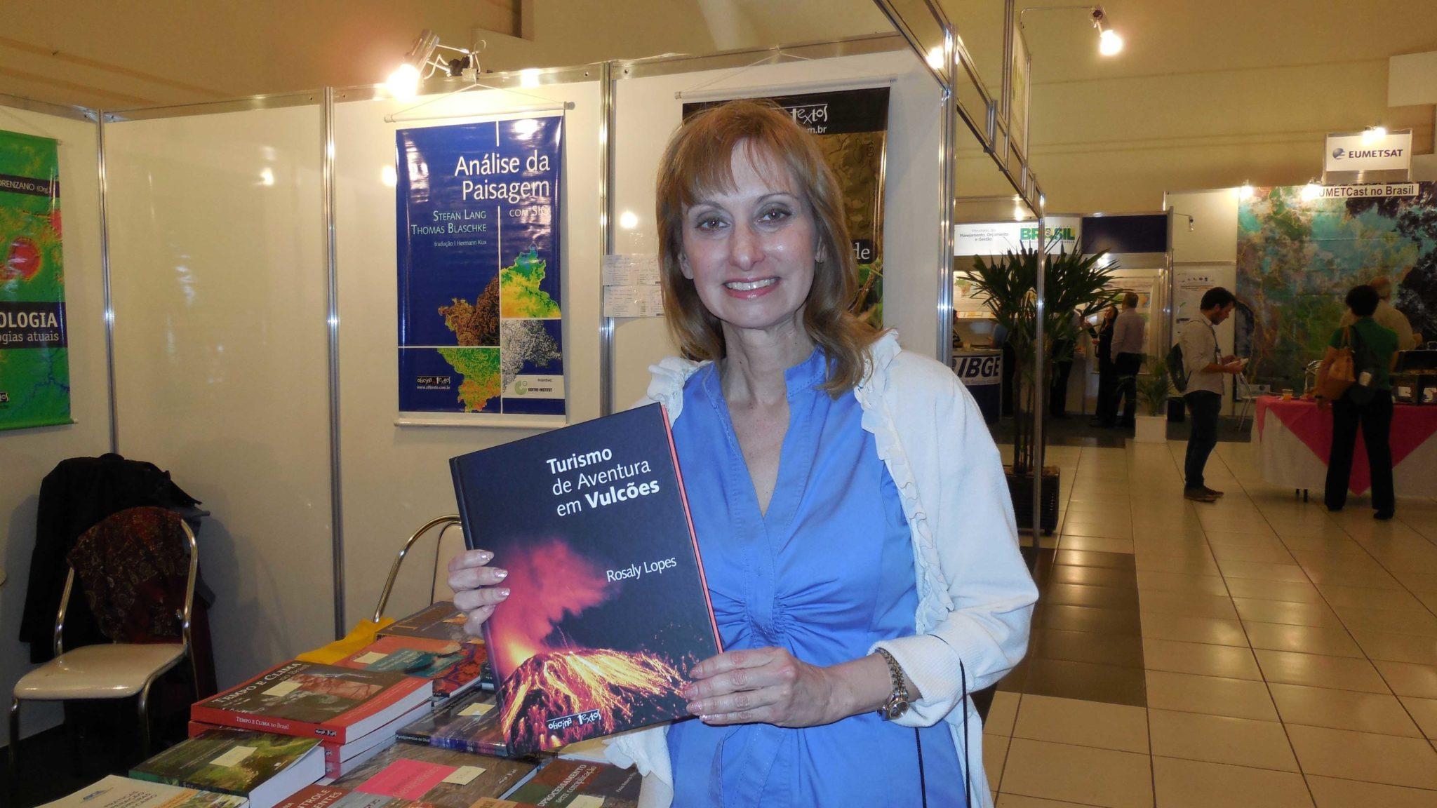 astrônoma brasileira rosaly lopes segura livro sobre vulcões feira científica