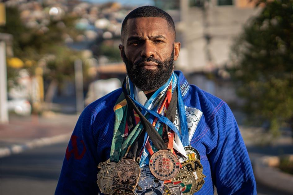 atleta jiu-jitsu segurando medalhas pescoço