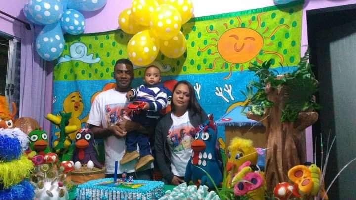 pais e filho em festa de aniversário com tema da galinha pintadinha