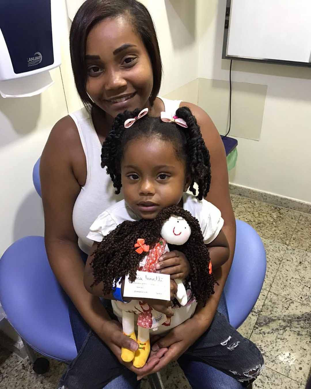 mãe com filha no colo segurando boneca terapêutica em hospital