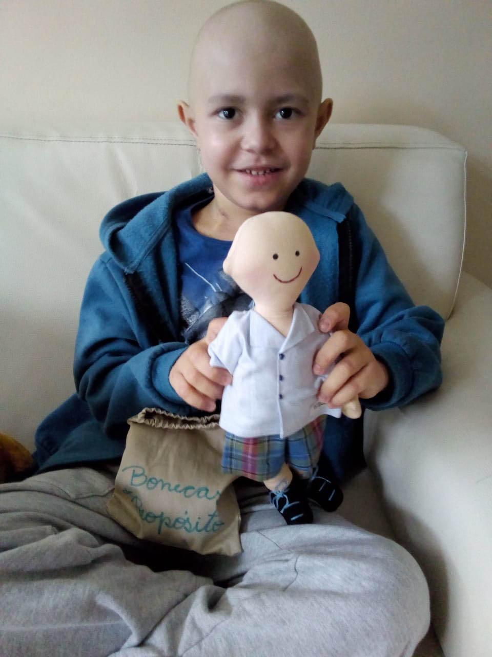 menino em tratamento contra o câncer segura boneca terapêutica