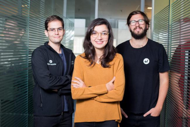 Mulher e dois homens em empresa posando para a foto