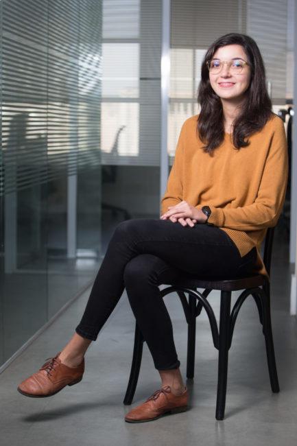 Empreendedora de startup sentada em cadeira com roupa marrom e preta e sorrindo