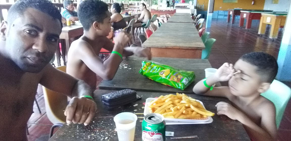 pai comendo lanche com dois filhos em lanchonete