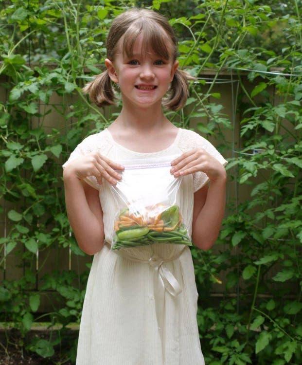 menina cultiva doa alimentos produzidos horta comunitária moradores rua