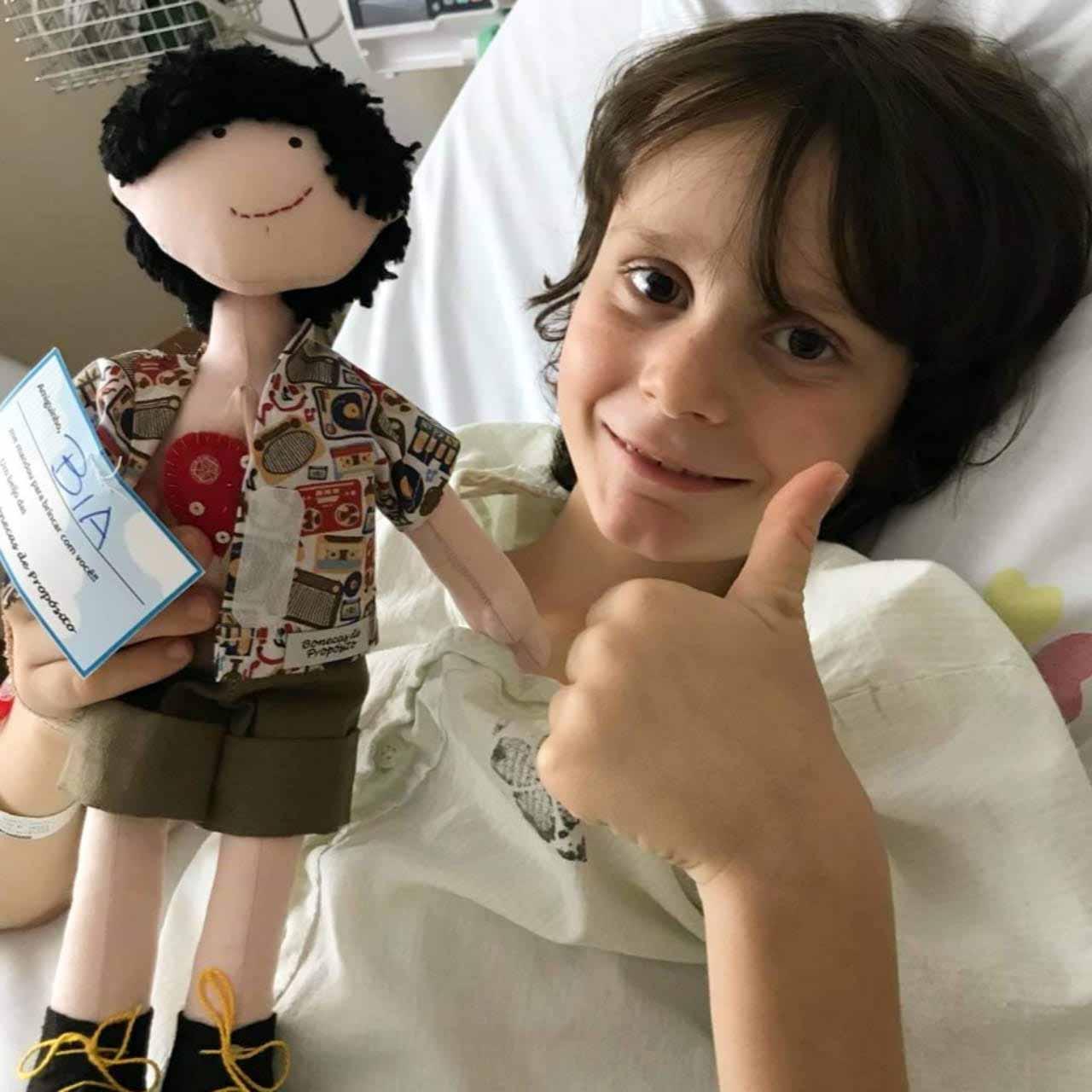 menino deitado leito hospital com boneca terapêutica