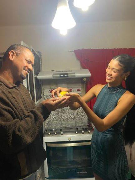 Homem recebendo presente de filha em cozinha com fogão