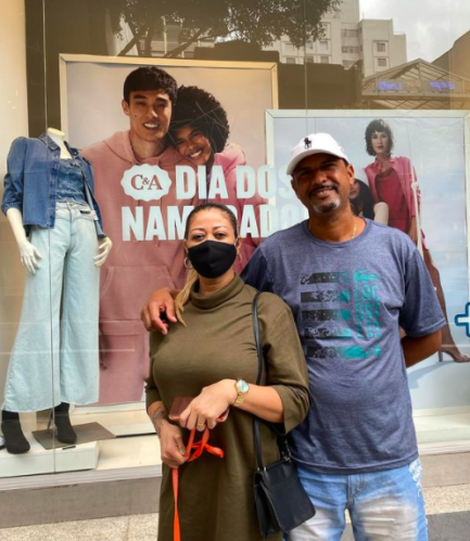 Homem e mulher à frente de vitrine de loja
