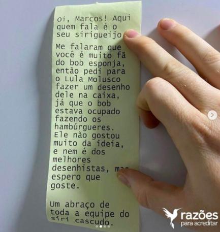 Mão segurando e exibindo cartinha escrita em nota de cupom fiscal