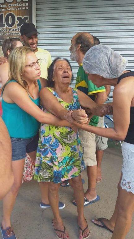 Foto de mulheres segurando idosa na rua que estava passando mal