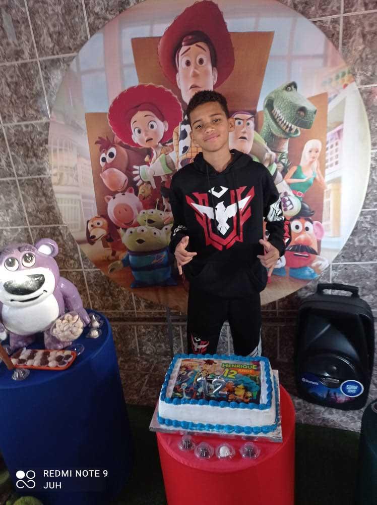 menino atrás do seu bolo de aniversário com tema toy story