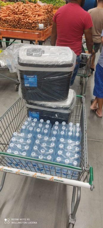 Fardos de água mineral e caixas térmicas em carrinho de supermercado