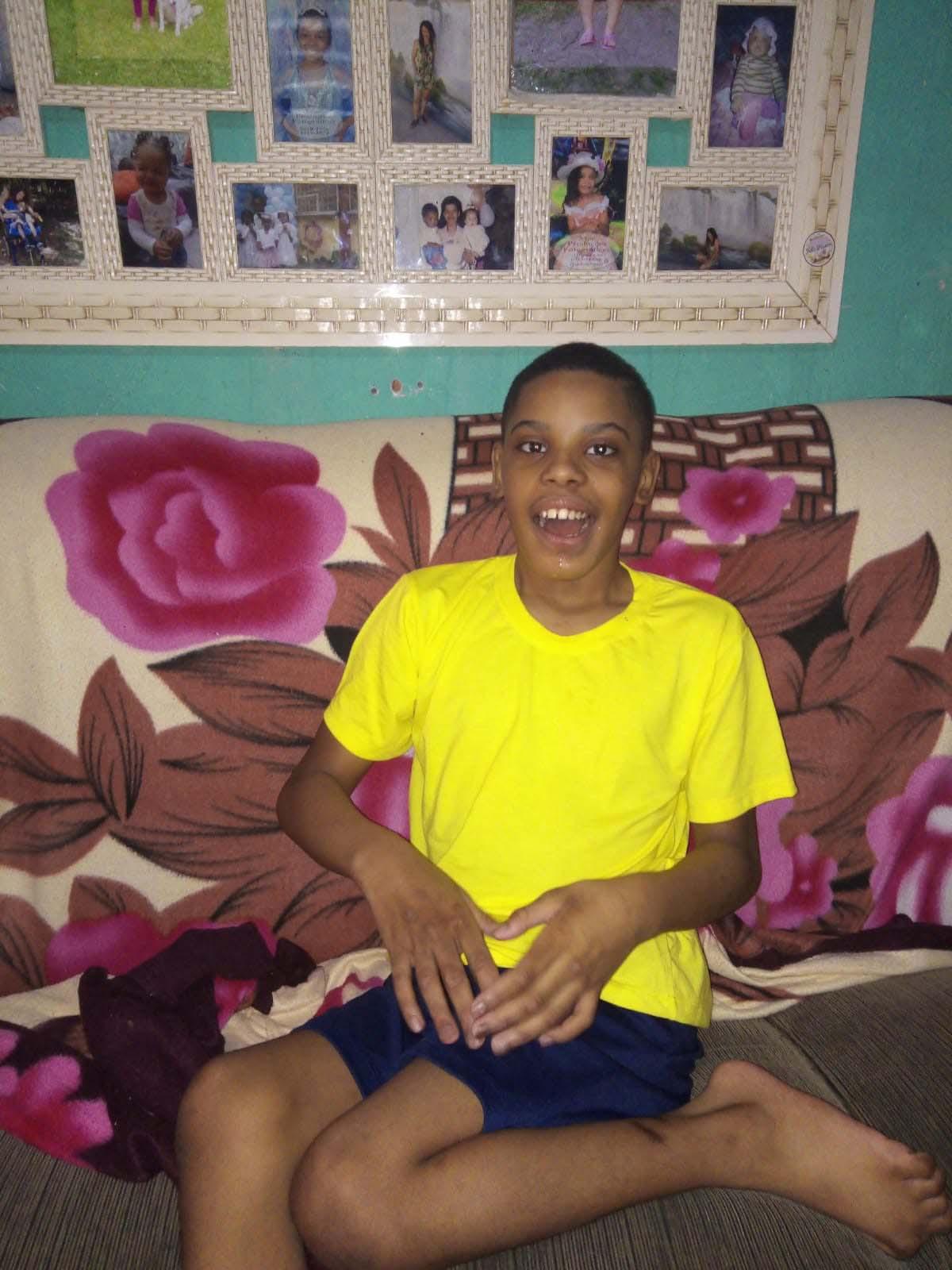 menino negro com poliomielite sentado em sofá