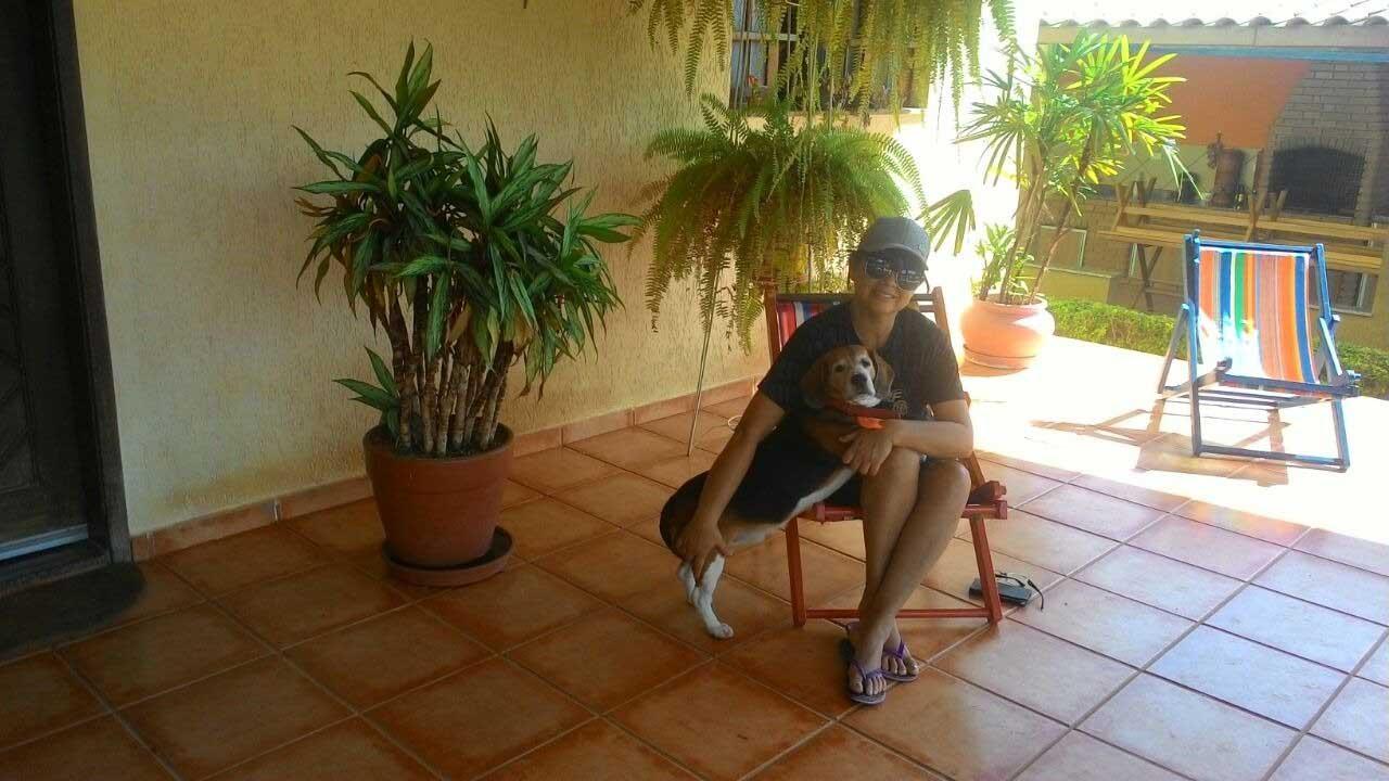mulher sentada em cadeira com seu cachorro na varanda de casa