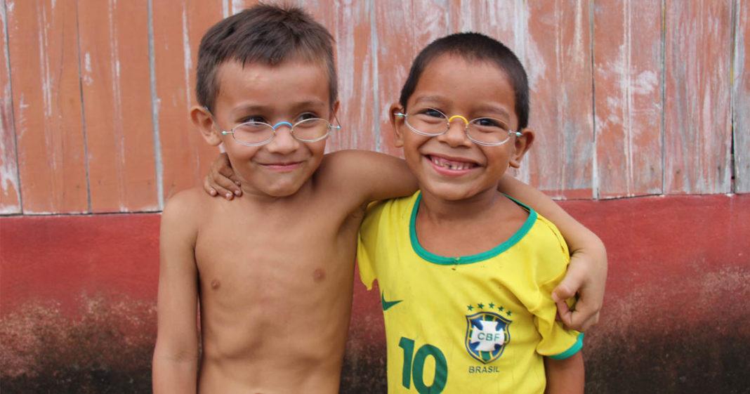 dois meninos usando óculos abraçados e sorrindo